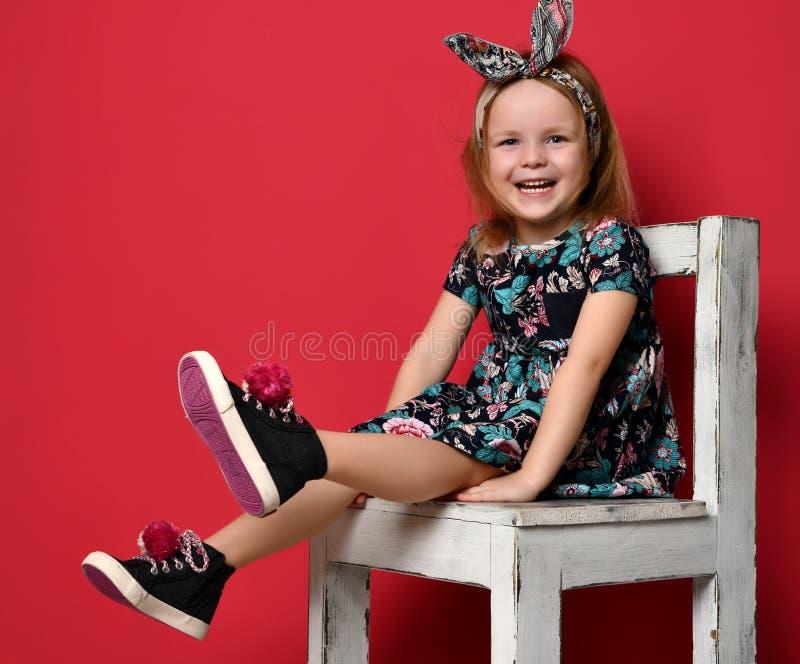 Criança bonito do bebê no vestido e na faixa do verão da forma que sentam-se no sorriso feliz da cadeira imagens de stock