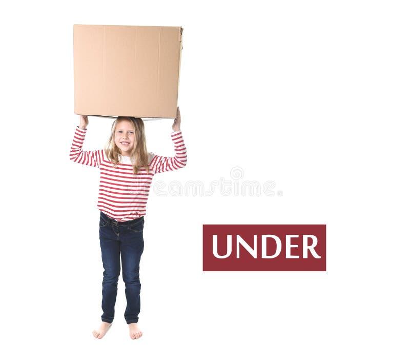 Criança bonito e doce do cabelo louro que está sob a caixa de cartão que aprende o grupo de cartão inglês foto de stock