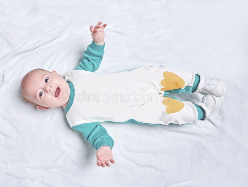 Criança bonito em um terno de pinguim que encontra-se em uma cobertura imagens de stock