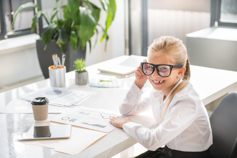 A criança bonito encantador está trabalhando no escritório imagem de stock