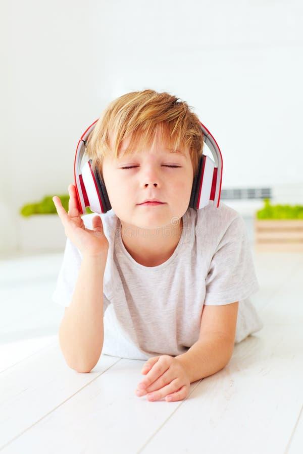 A criança bonito escuta a música, relaxando em casa imagens de stock