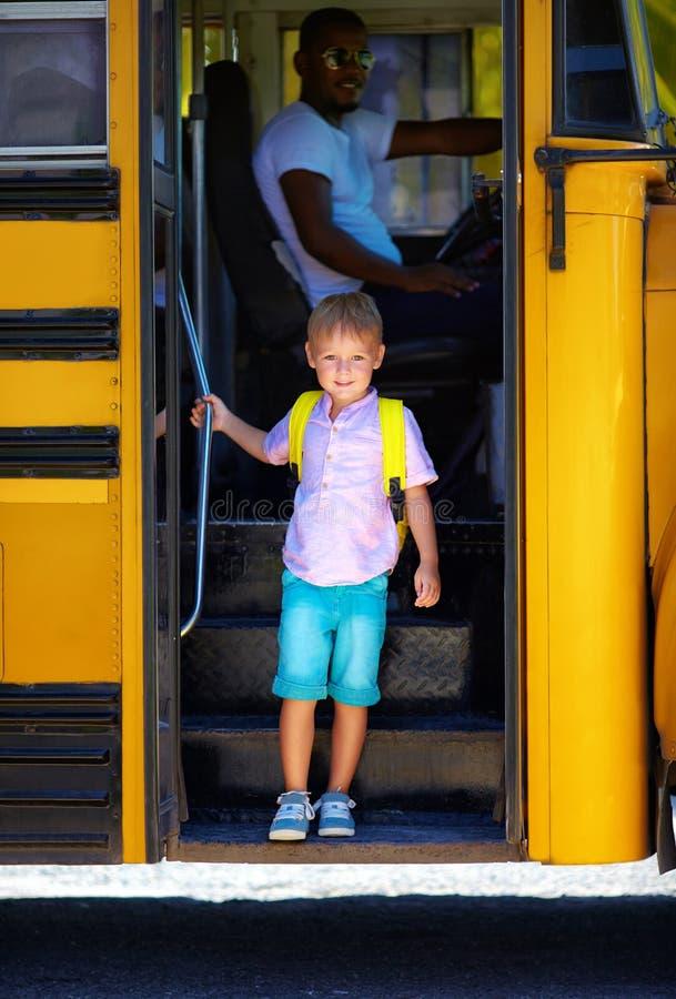 A criança bonito está pegando fora o ônibus, após a escola fotografia de stock