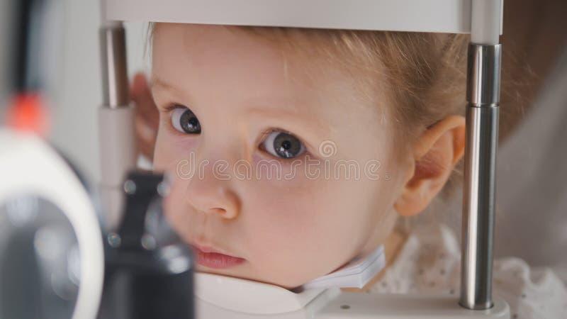 Criança bonito na clínica da oftalmologia - menina loura pequena do diagnóstico do optometrista imagem de stock royalty free