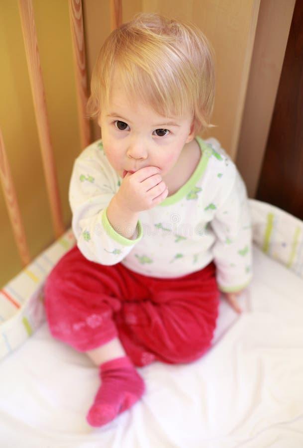 Criança bonito na ucha que suga seu dedo fotos de stock