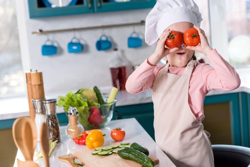 criança bonito no chapéu do cozinheiro chefe e avental que guarda tomates ao cozinhar fotos de stock