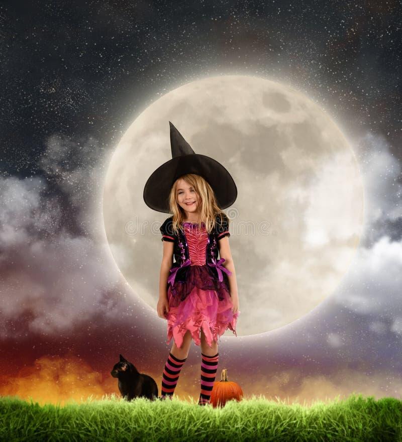 Criança bonito no traje da bruxa de Dia das Bruxas na frente da lua imagens de stock royalty free