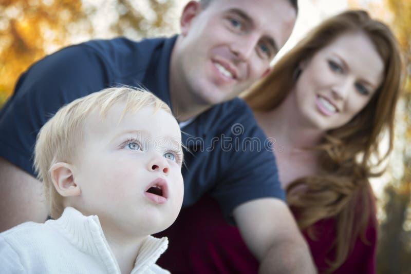 A criança bonito olha acima ao céu enquanto os pais novos sorriem fotografia de stock royalty free