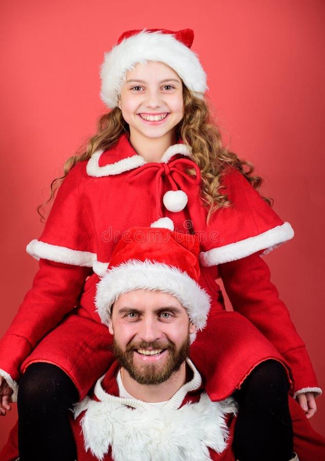 A criança bonito pequena da menina e o pai farpado vestem o traje de Santa Como ser guia dos pais de Papai Noel Meu paizinho é Pa foto de stock royalty free