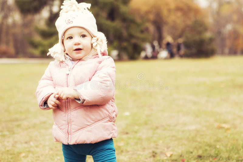 Criança bonito pequena da menina que tem o divertimento no parque na roupa morna do outono & no x28; fotografia de stock royalty free