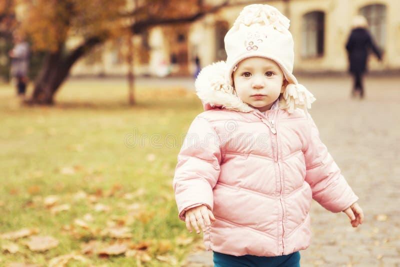 Criança bonito pequena da menina que tem o divertimento no parque na roupa morna do outono & no x28; imagem de stock royalty free