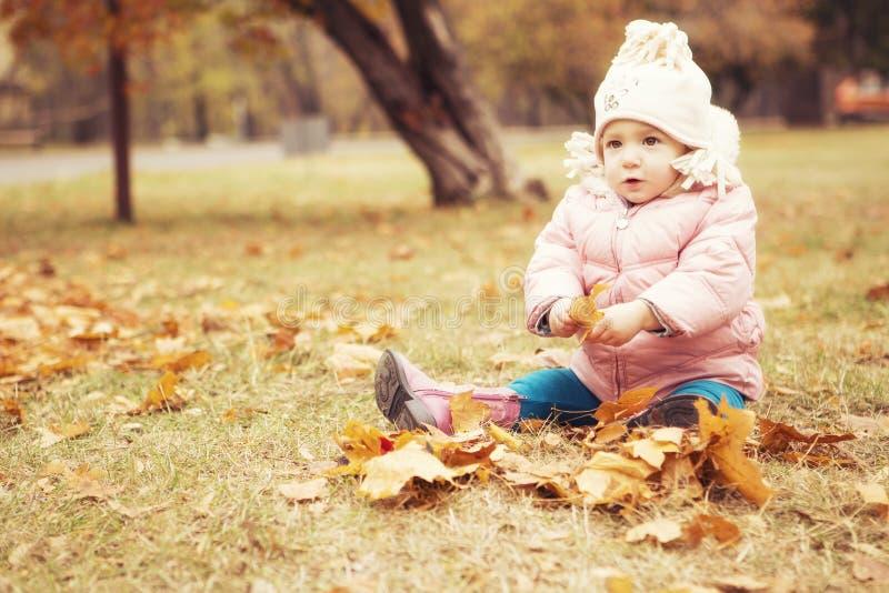 Criança bonito pequena da menina que tem o divertimento no parque na roupa morna do outono & no x28; foto de stock