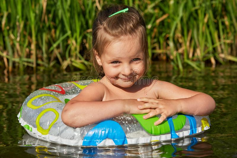 Criança bonito pequena que tem o resto durante as férias de verão, tentando nadar com círculo nadador, relaxando no rio perto do  fotografia de stock