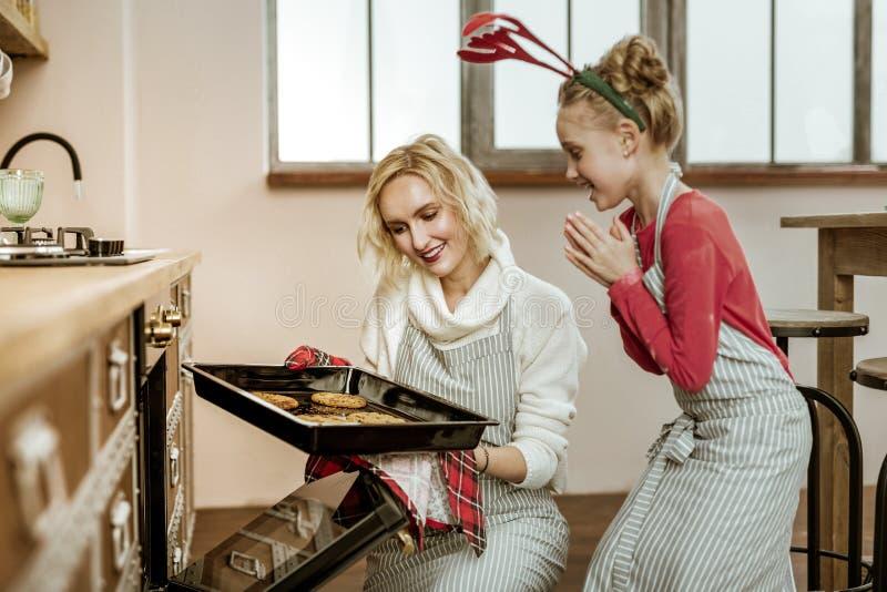 Criança bonito positiva no vestido vermelho e no avental listrado que indicam a massa crua imagem de stock royalty free
