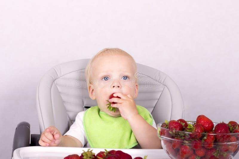 Criança bonito que come a morango Bebê engraçado com uma morango em seu braço fotos de stock