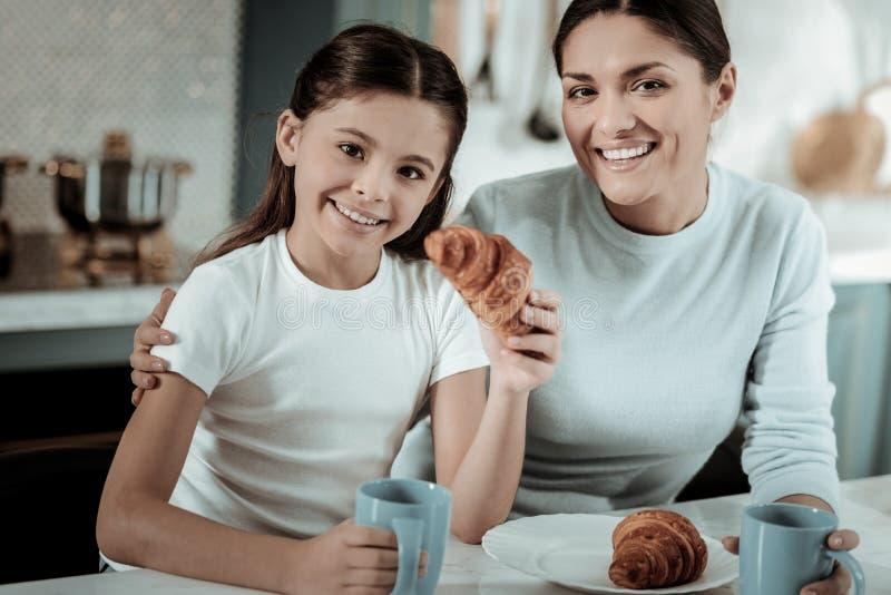 Criança bonito que come o café da manhã com a mãe na cozinha fotografia de stock
