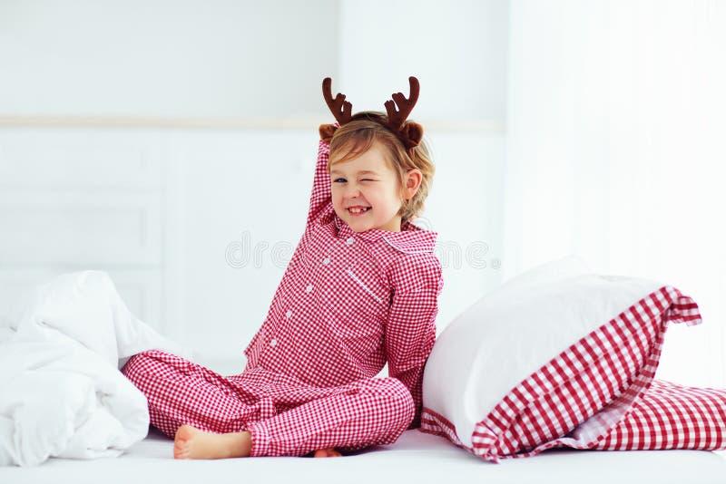 Criança bonito que faz as caras engraçadas na manhã com chifres da rena, feriados do inverno do Natal foto de stock