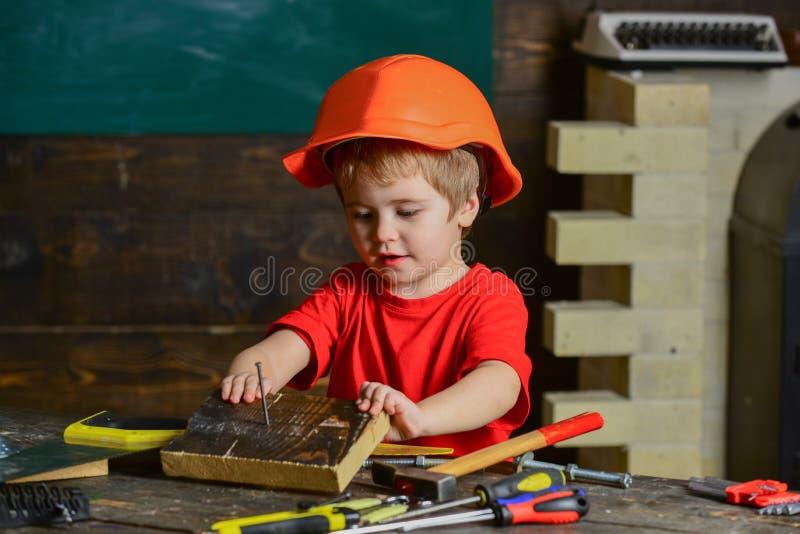 Criança bonito que joga com conjunto de ferramentas Carpinteiro pequeno que trabalha com bloco de madeira Menino pequeno na ofici imagem de stock royalty free