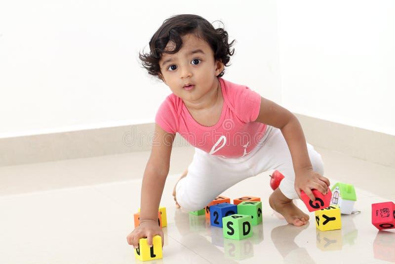 Criança bonito que joga com os cubos do alfabeto da espuma imagem de stock royalty free