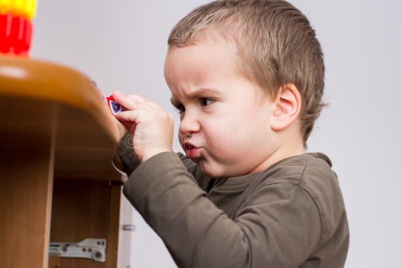 Criança bonito que joga na mesa com brinquedo do carro foto de stock