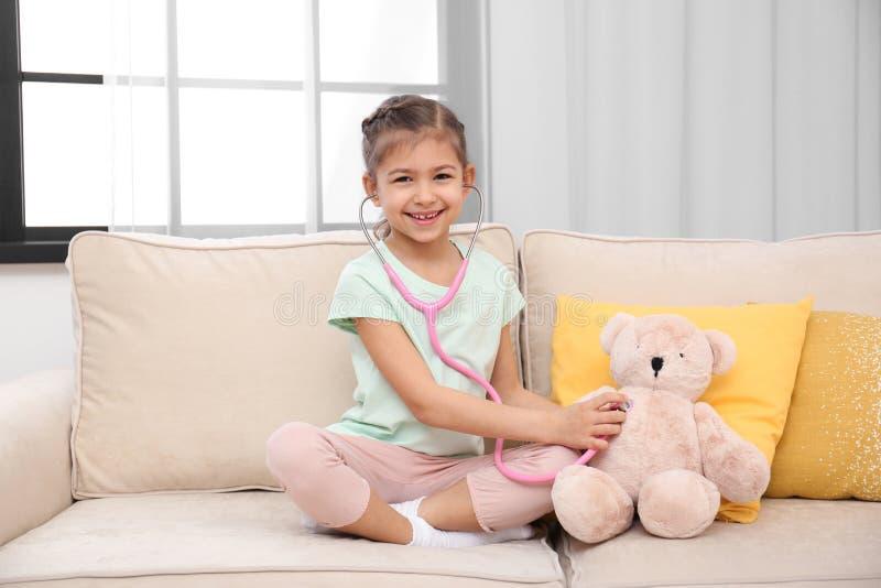 Criança bonito que joga o doutor com o brinquedo enchido no sofá fotos de stock royalty free