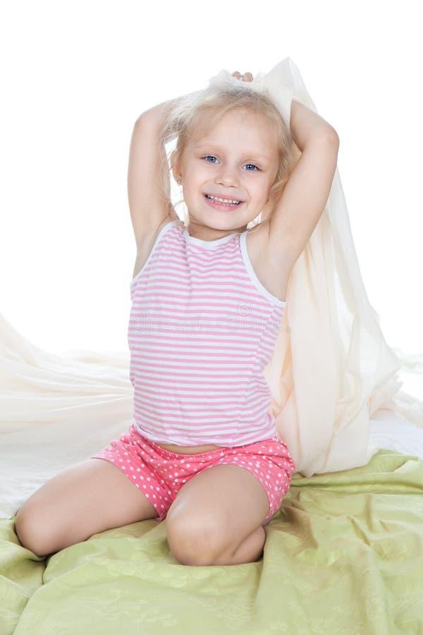 Criança bonito que senta-se na cama fotos de stock