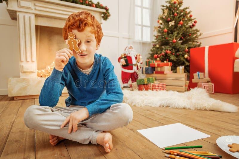Criança bonito relaxado que joga com homem de pão-de-espécie em casa fotos de stock royalty free