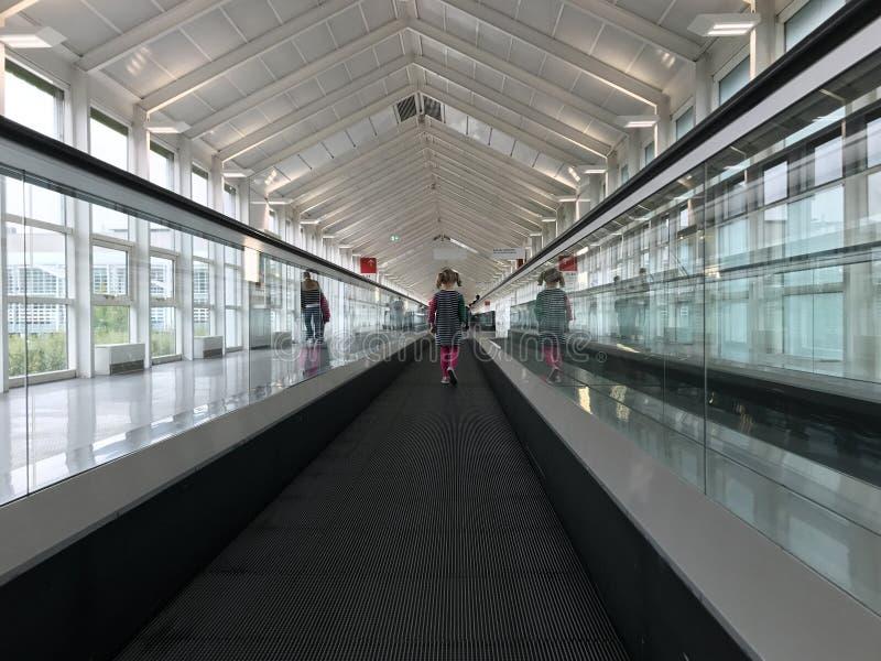 Criança bonito só que viaja no travelator no terminal de aeroporto fotografia de stock royalty free