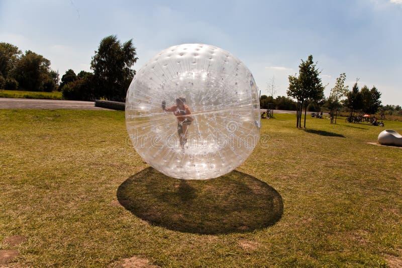 A criança bonito tem muito divertimento na esfera de Zorbing foto de stock royalty free