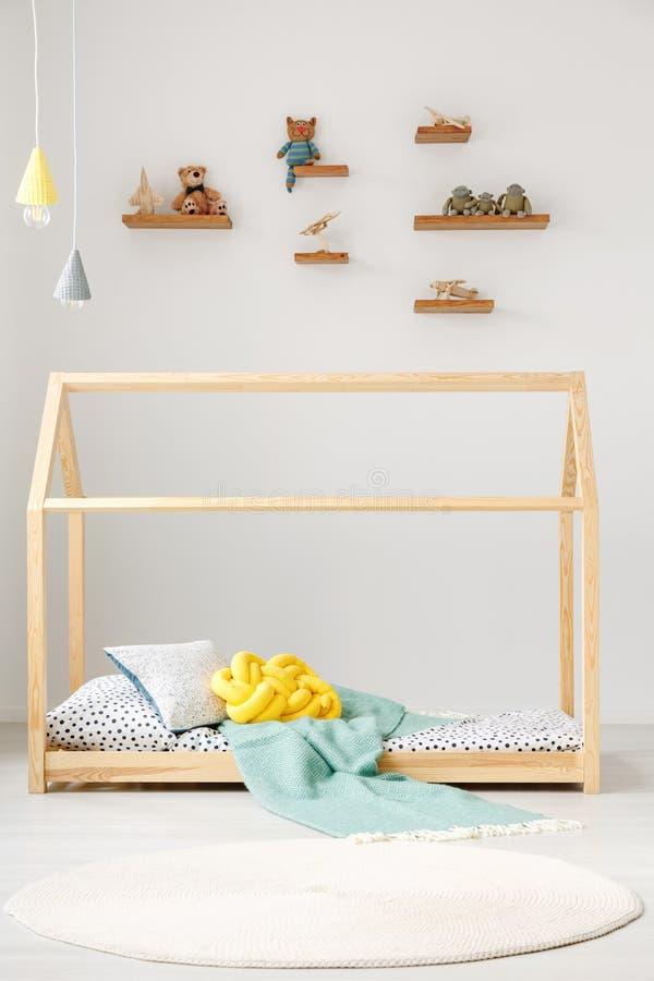A criança brinca em prateleiras em uma parede branca e em uma cama de madeira fra da casa fotos de stock