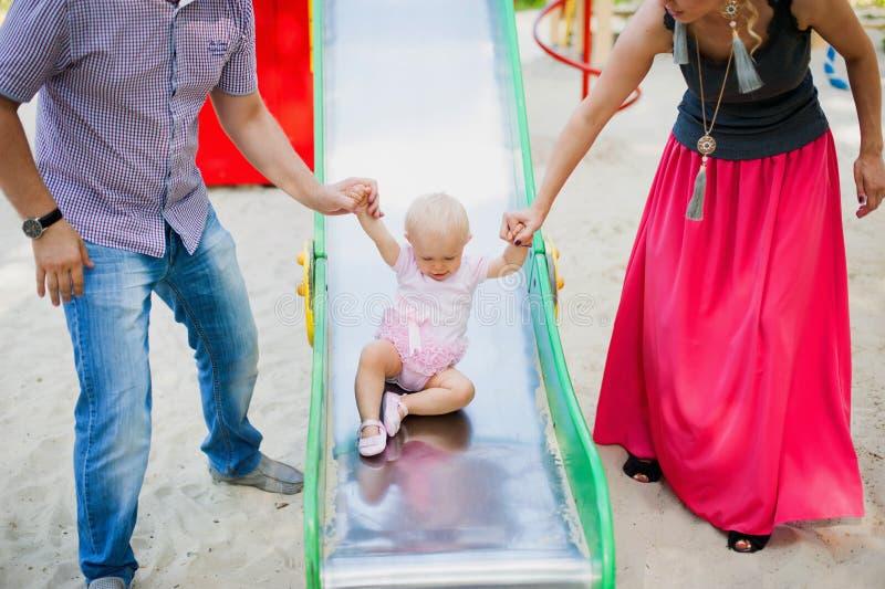 Criança brincalhão com pais no campo de jogos exterior imagem de stock royalty free
