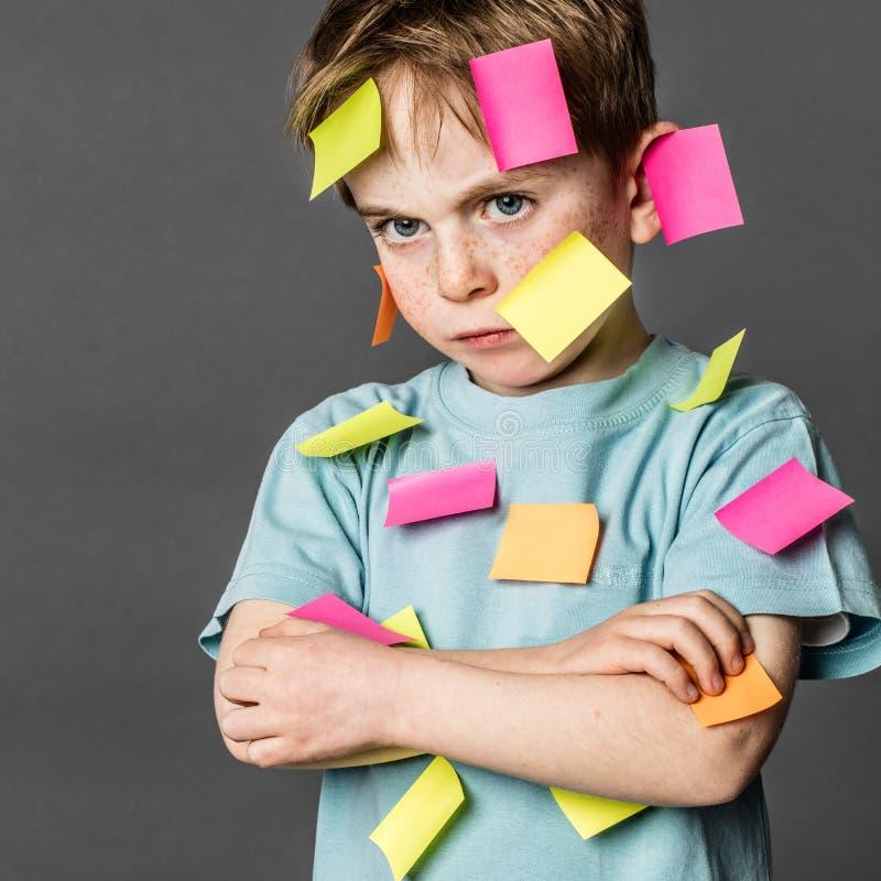 Criança cansado que amua com os braços cruzados com notas na cara imagem de stock royalty free