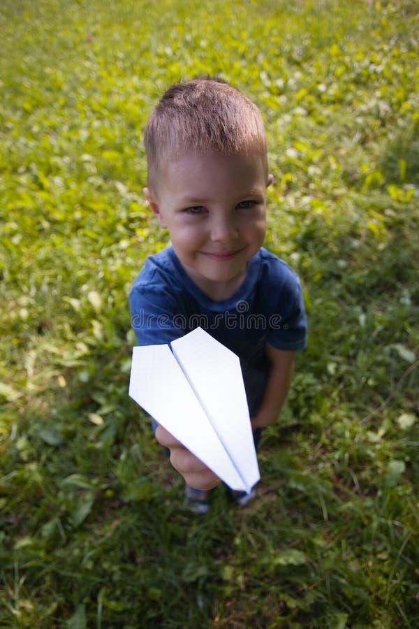 Criança caucasiano bonito que joga o avião de papel no parque fora no dia ensolarado do verão foto de stock