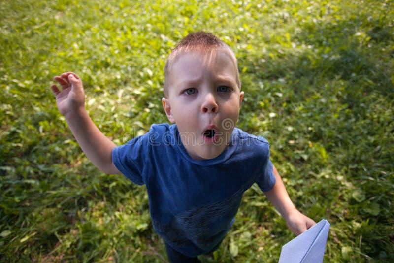 Criança caucasiano bonito que joga o avião de papel no parque fora no dia ensolarado do verão imagem de stock