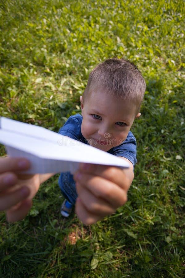 Criança caucasiano bonito que joga o avião de papel no parque fora no dia ensolarado do verão fotografia de stock