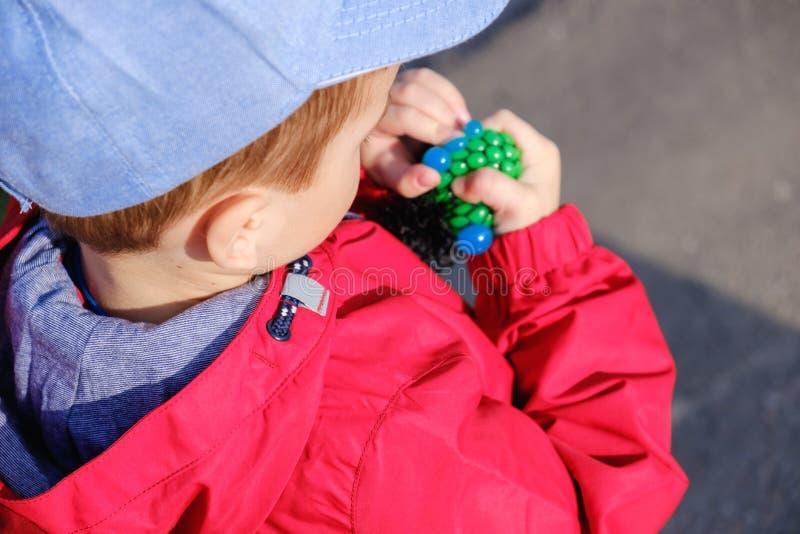 A criança caucasiano bonito que joga o brinquedo feito à mão chamou o limo fotografia de stock royalty free