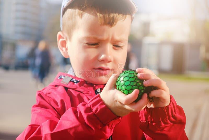 A criança caucasiano bonito que joga o brinquedo feito à mão chamou o limo imagens de stock