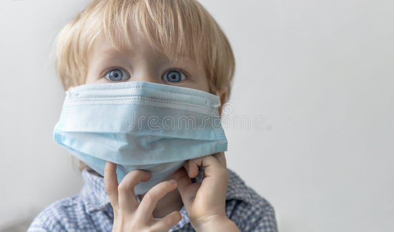 Criança caucasiano da criança da criança do menino de Europeanan loura na máscara médica azul no fundo cinzento Conceito do vírus fotos de stock