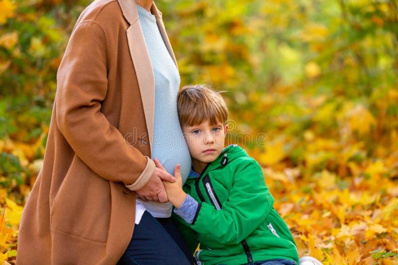 Criança caucasiano doce bonito que escuta a barriga da sua mãe grávida que espera o bebê que agita na barriga expectativas imagens de stock