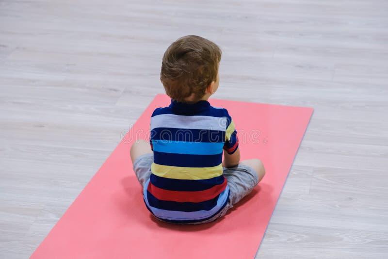 A criança caucasiano que exercita em esteiras no gym, crianças da ioga ostenta fotos de stock royalty free