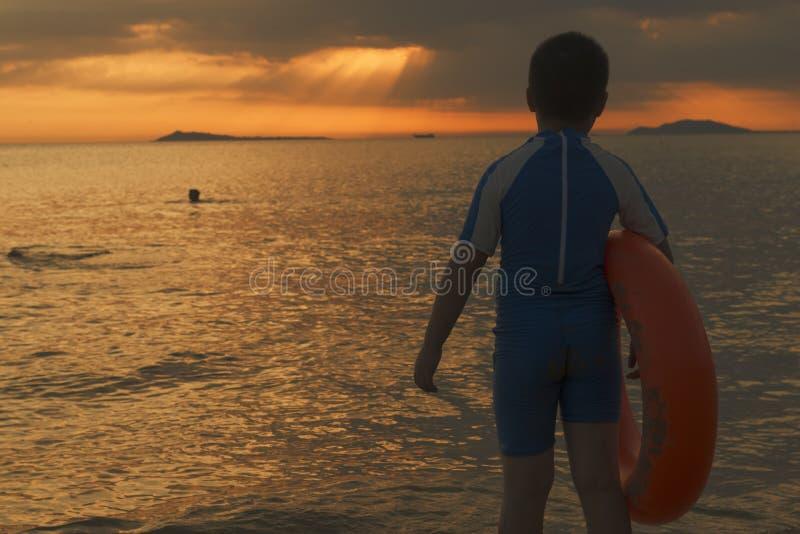 Crian?a chinesa com anel nadador no tempo do por do sol da praia imagens de stock royalty free
