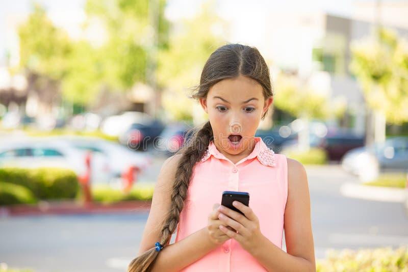 Criança chocada que texting no telefone móvel, esperto foto de stock royalty free
