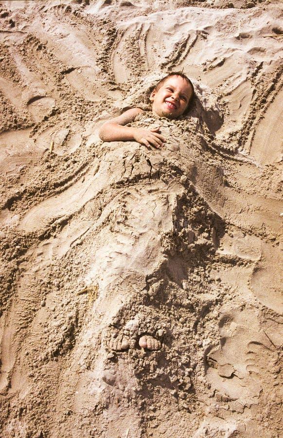 Criança coberta com a areia fotos de stock