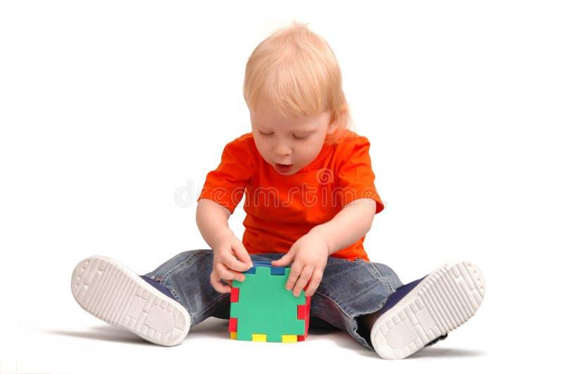 A criança coleta o cubo dos enigmas imagens de stock