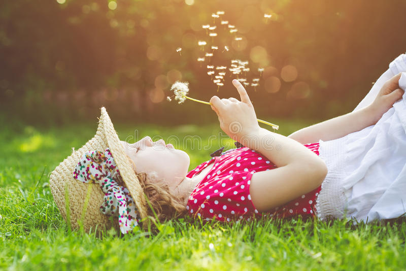 A criança coloca em uma grama e em um dente-de-leão de sopro nos raios de t imagem de stock