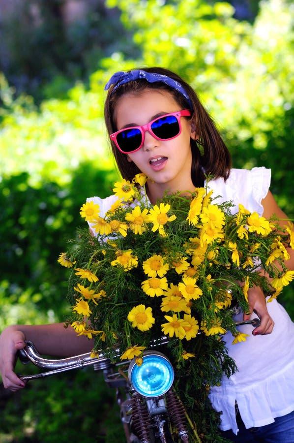 Criança com bicicleta e flores e óculos de sol fotografia de stock royalty free