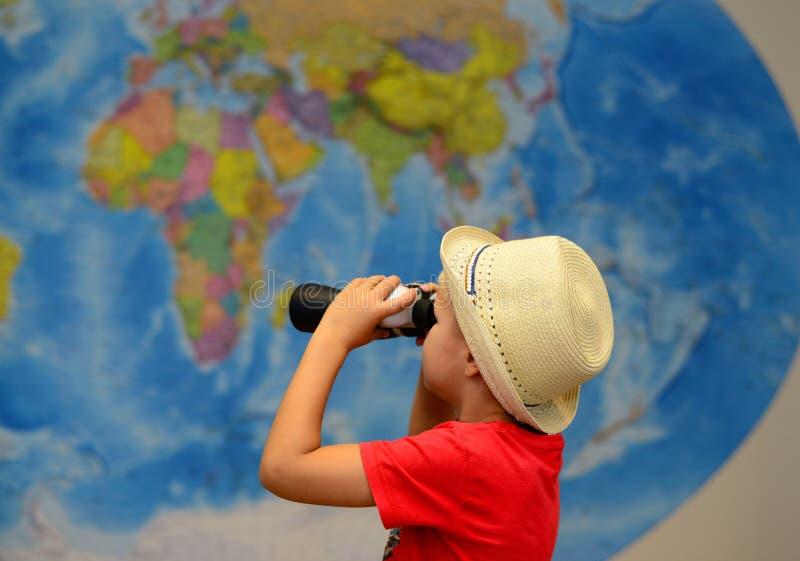 A criança com binóculos está jogando nos viajantes Conceito da aventura e do curso Fundo creativo foto de stock royalty free