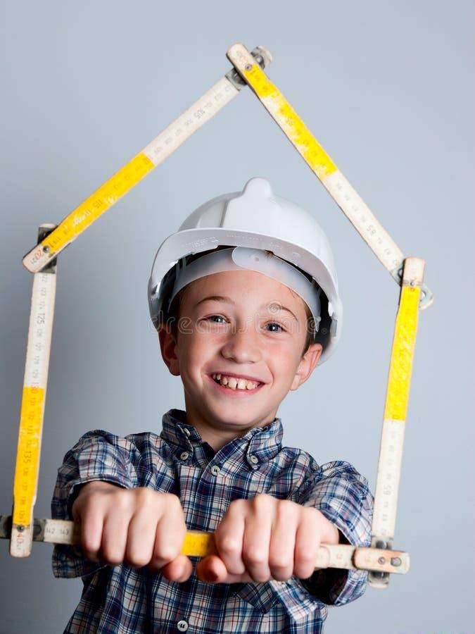Criança com capacete e a casa brancos foto de stock royalty free