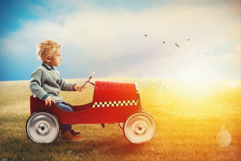 A criança com carro joga em um campo verde fotografia de stock