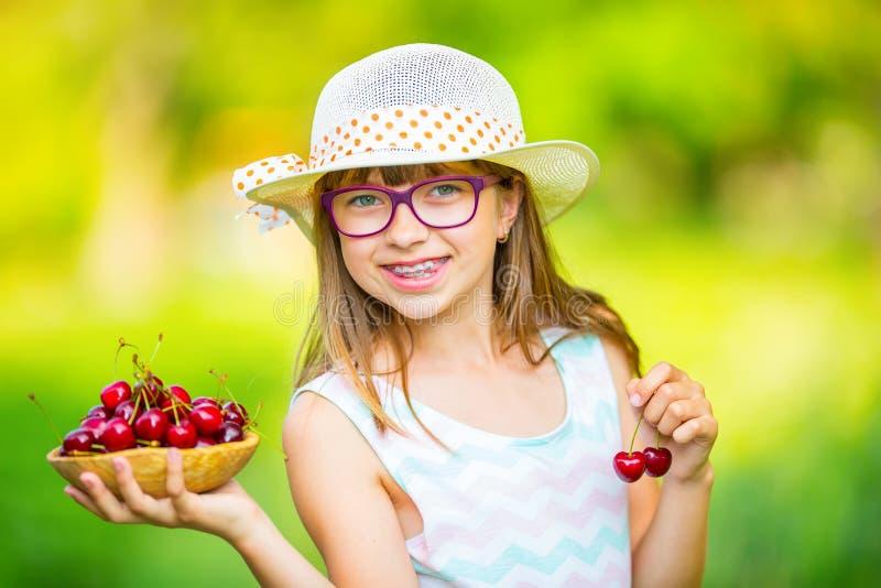 Criança com cerejas Menina com cerejas frescas Cintas e vidros vestindo dos dentes da menina loura caucasiano bonito nova imagem de stock