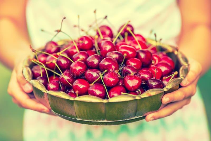 Criança com cerejas Menina com cerejas frescas Cintas e vidros vestindo dos dentes da menina loura caucasiano bonito nova fotografia de stock